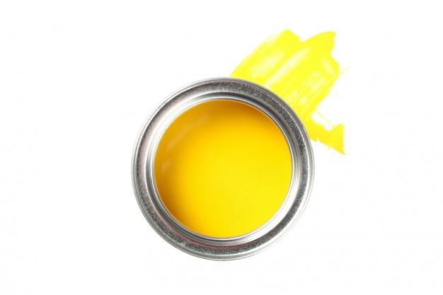 Lattina di vernice gialla e tratto isolato su superficie bianca