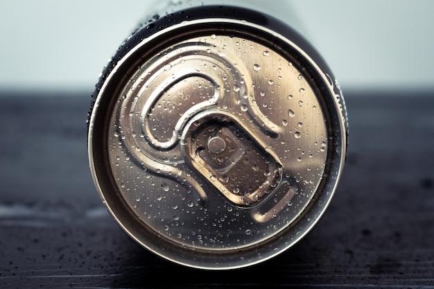 Lattina per bevande in metallo con gocce d'acqua. la cola lucida può primo piano. bottiglia d'oro di bevanda, coperchio della confezione di soda, tonico. vista dall'alto.