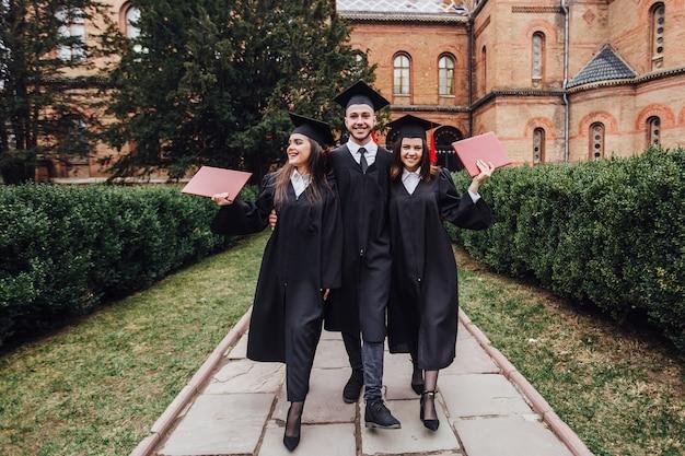 Laureati di successo con il loro diploma che camminano nel giardino dell'università