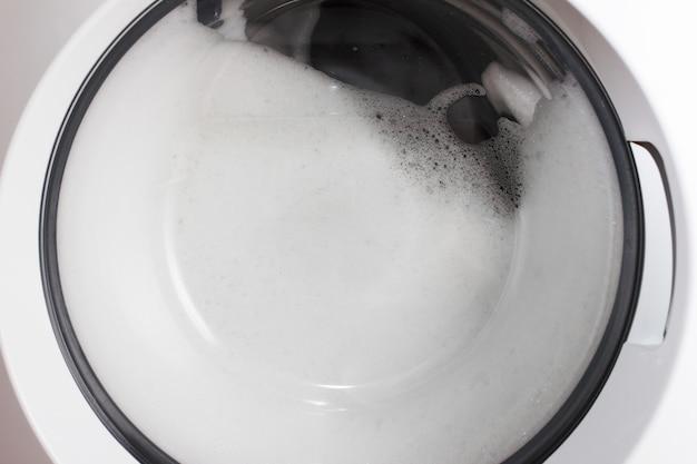 Lavaggio a casa. abbigliamento e schiuma nel cestello della lavatrice