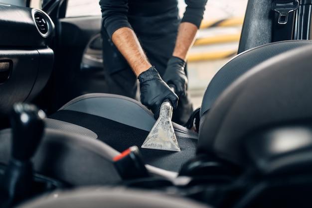Lavaggio a secco degli interni dell'auto con aspirapolvere