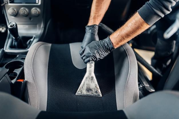 Lavaggio a secco professionale degli interni dell'auto con aspirapolvere.