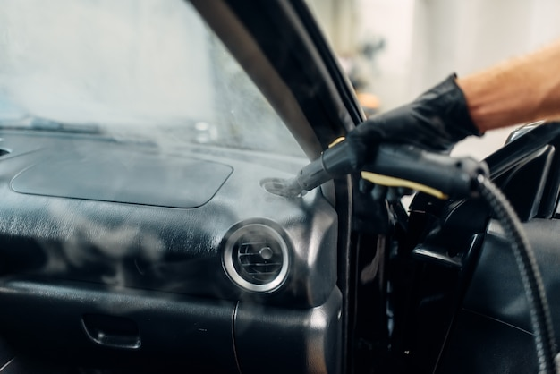 Lavaggio a secco professionale del condotto dell'aria dell'auto con pulitore a vapore. servizio di autolavaggio, igiene del salone del veicolo, lavoratore maschio rimuove sporco e polvere