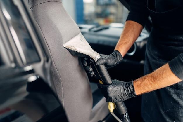 Lavaggio a secco professionale di seggiolini auto con aspirapolvere.