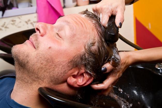 Lavaggio capelli uomo nel salone di bellezza parrucchiere