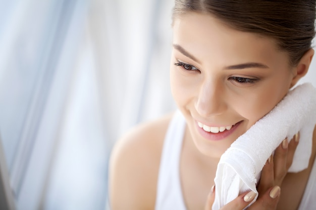 Lavaggio del viso, primo piano della donna felice asciugare la pelle con un asciugamano