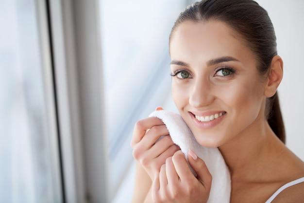 Lavaggio del viso. primo piano della pelle di secchezza della donna felice con l'asciugamano.
