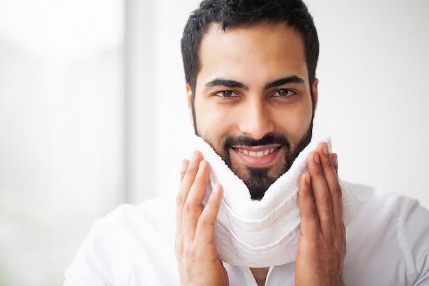 Lavaggio del viso. uomo felice che asciuga pelle con asciugamano