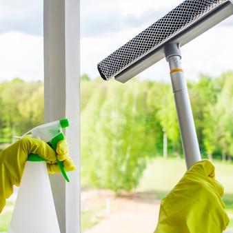 Lavaggio delle finestre e pulizia della casa. la governante in guanti lava e pulisce il vetro sporco.