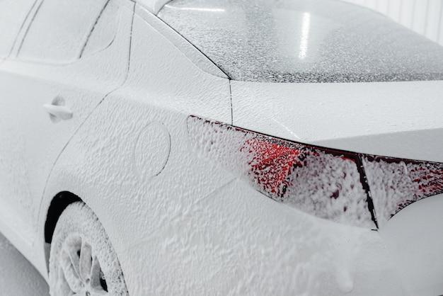Lavaggio moderno con schiuma e acqua ad alta pressione della macchina bianca.