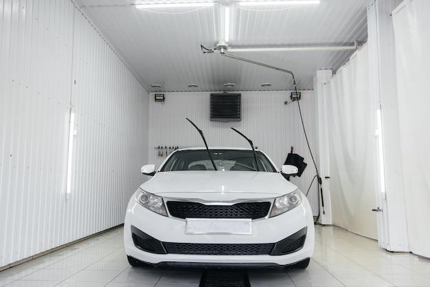 Lavaggio moderno con schiuma e acqua ad alta pressione di un'auto bianca. autolavaggio.