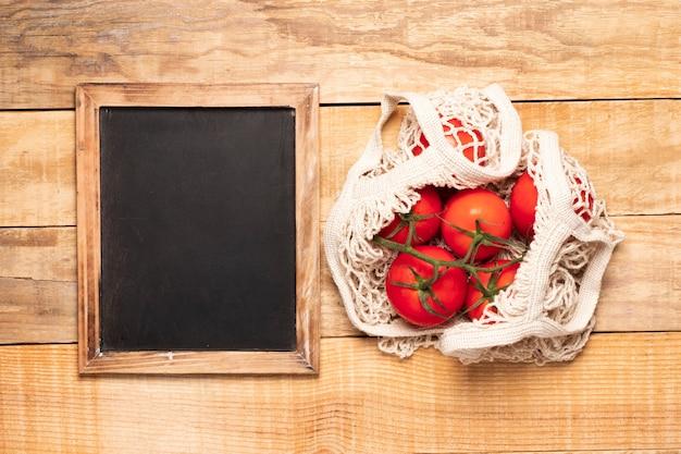 Lavagna accanto al sacco di pomodori