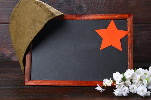 Lavagna, berretto militare e stella rossa su un tavolo. giorno del difensore della patria e il 9 maggio.