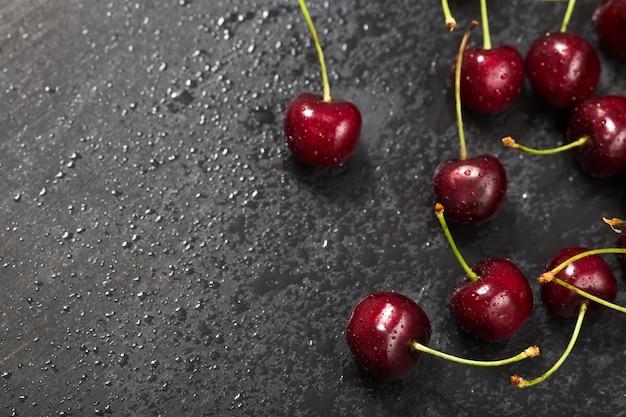Lavagna, ciliegie fresche, gocce d'acqua