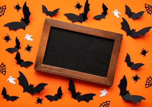 Lavagna circondata da pipistrelli di carta