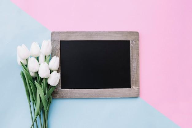 Lavagna con bouquet di tulipani su sfondo rosa e blu chiaro