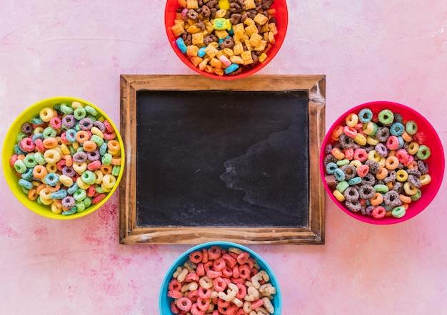Lavagna con ciotole di cereali sul tavolo