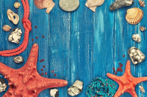 Lavagna con cornice in conchiglie, pietre, corda e pesci stelle su legno blu