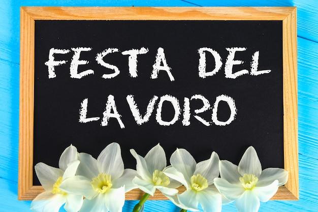 Lavagna con il testo in italiano: festa del lavoro. festa del lavoro e primavera, 1 maggio.