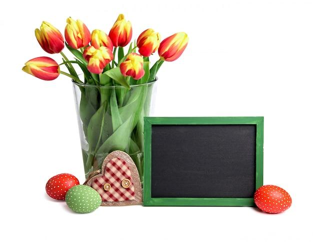 Lavagna con lo spazio del testo, mazzo di tulipani a righe rosse in vaso di vetro,