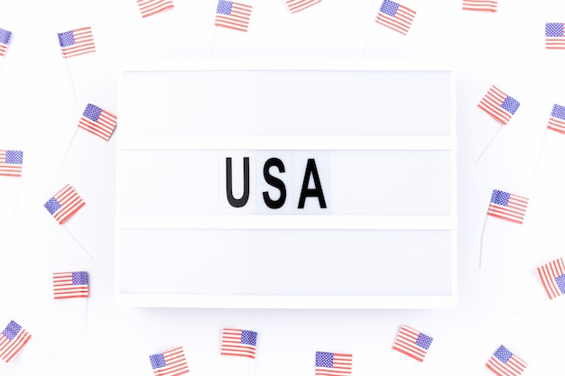Lavagna con nota usa circondata da piccole bandiere americane