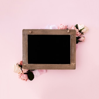 Lavagna con rose rosa su sfondo rosa