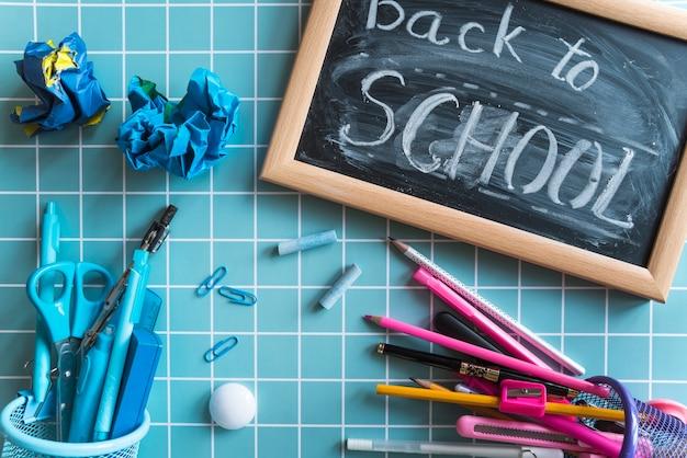 Lavagna con testo torna a scuola e articoli di cancelleria