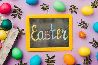 Lavagna con titolo di Pasqua tra set di uova colorate e foglie vicino contenitore