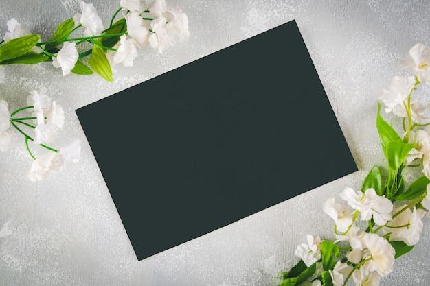 Lavagna con un campo vuoto circondato da fiori bianchi su uno sfondo grigio.
