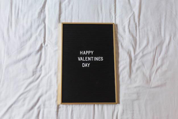 Lavagna d'annata con il messaggio felice di san valentino più con fondo. a casa, al chiuso. concetto