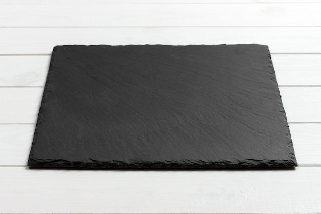 Lavagna dell'ardesia sulla tavola di legno
