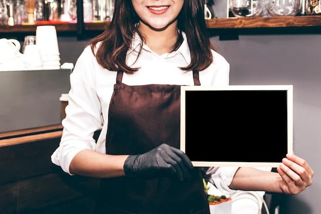Lavagna della tenuta di barista nel ristorante della caffetteria