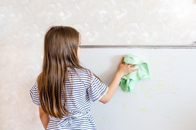 Lavagna di pulizia della ragazza con lo straccio
