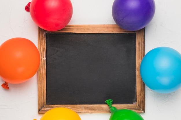 Lavagna e palloncini luminosi nei colori lgbt
