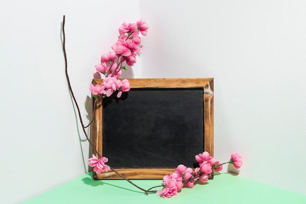 Lavagna in bianco con ramo di fiori sul tavolo