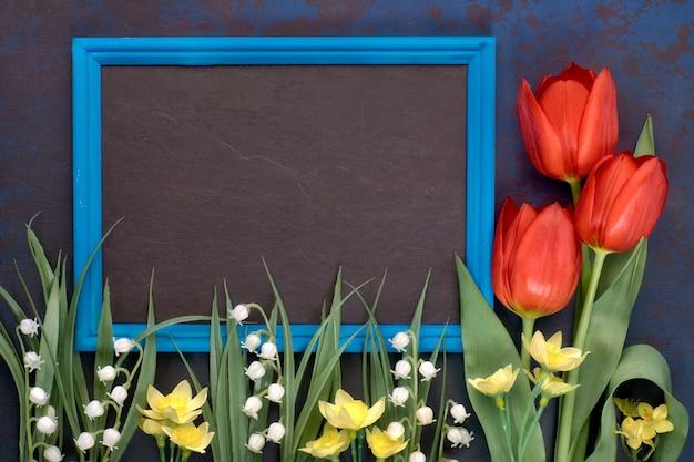 Lavagna in cornice blu con tulipani rossi e fiori di mughetto su oscurità