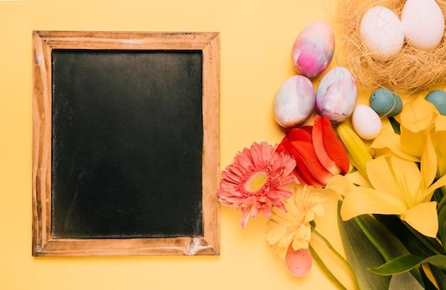 Lavagna in legno con uova di pasqua e fiori freschi sul contesto giallo