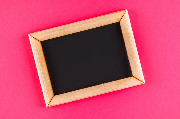 Lavagna in una cornice di legno con una scatola vuota su uno sfondo rosa. copia spazio