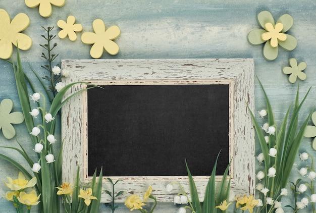 Lavagna incorniciata con fiori di primavera sul tavolo neutro, spazio per il testo