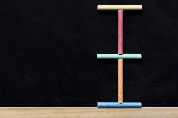 Lavagna nera con cornice in legno e gessetti colorati. di nuovo al fondo della lavagna della scuola