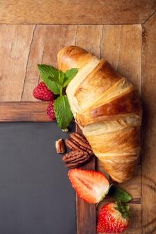 Lavagna nera con croissant e frutti di bosco