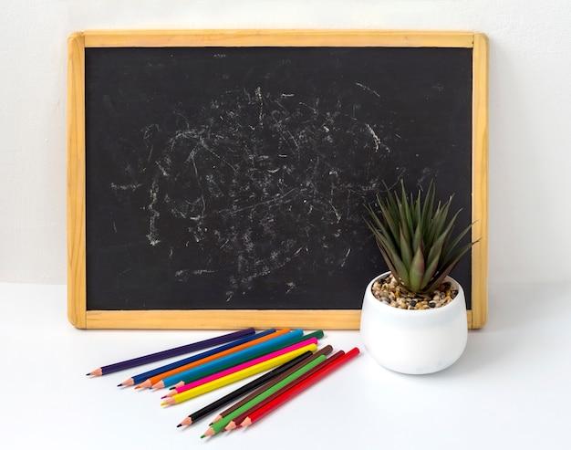 Lavagna nera per bambini con matite e un fiore su uno sfondo bianco con una copia dello spazio.