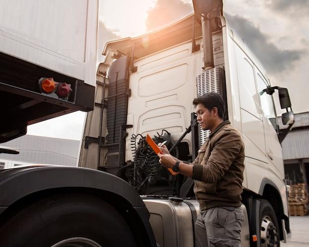 Lavagna per appunti asiatica della tenuta dell'autista di camion che ispeziona la lista di controllo di manutenzione del veicolo di sicurezza del camion moderno dei semi