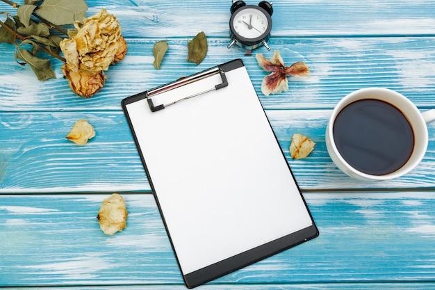 Lavagna per appunti con carta in bianco bianca sulla tavola di superficie di legno blu, vista superiore