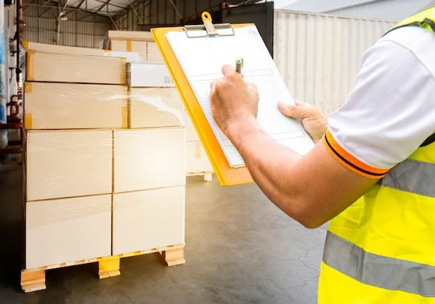 Lavagna per appunti della tenuta del lavoratore del magazzino il suo controllo al controllo del carico della spedizione con un camion.