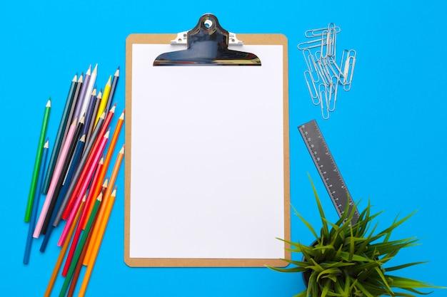Lavagna per appunti e articoli per ufficio sul blu. vista dall'alto. spazio per il testo