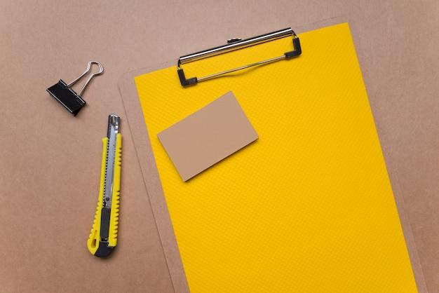 Lavagna per appunti gialla con il biglietto da visita di affari della cancelleria