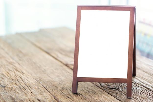 Lavagna pubblicitaria con cavalletto in piedi sul tavolo di legno