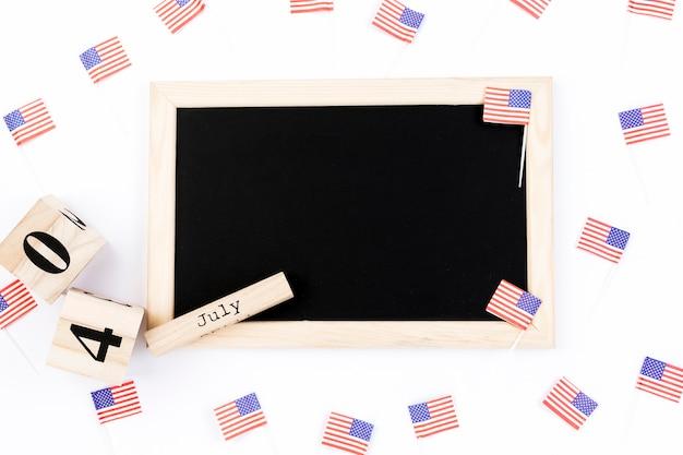 Lavagna su sfondo bianco circondato da piccole bandiere usa