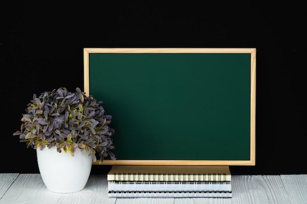 Lavagna verde con pila di carta notebook, articoli di cancelleria o materiale scolastico.
